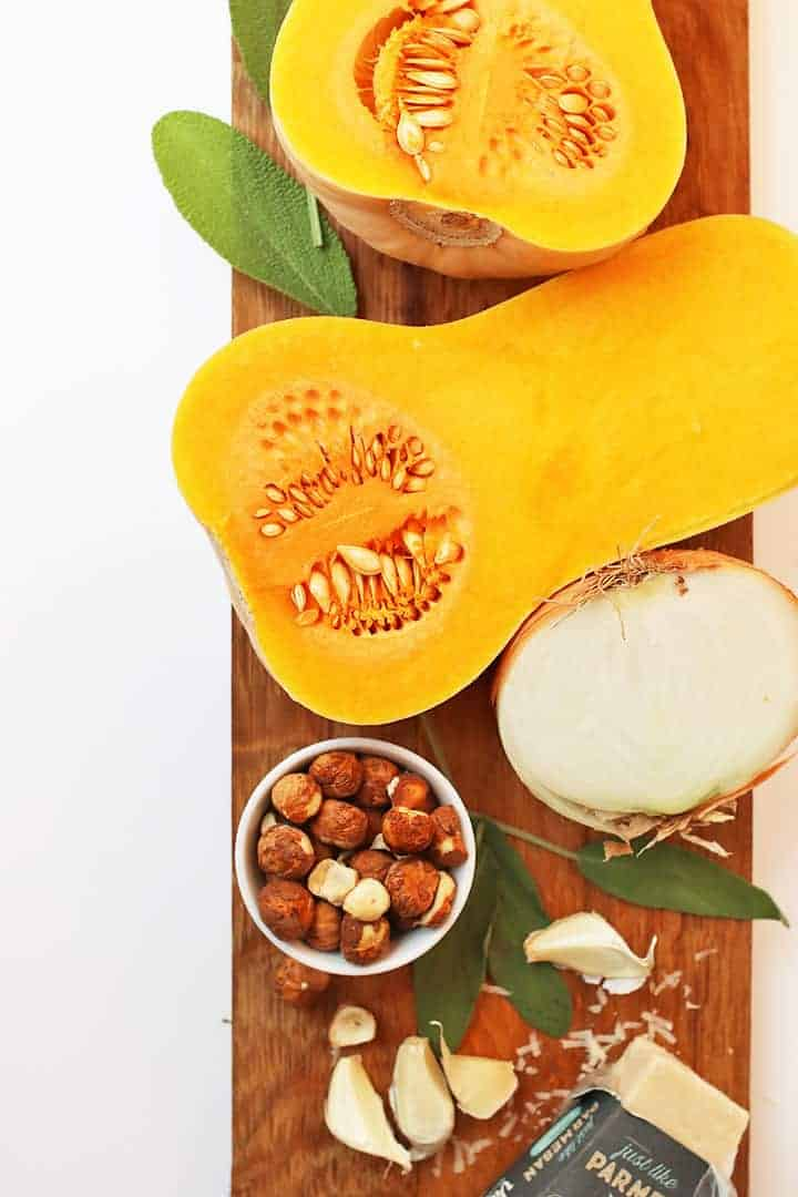 Butternut squash cut into half, onions, and hazelnuts on a cutting board.