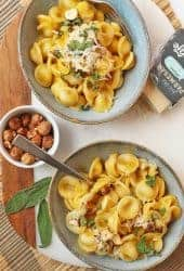 Two bowls of creamy Butternut Squash Pasta with toasted hazelnuts.