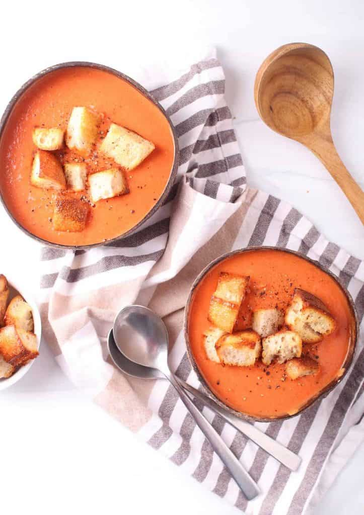 Two bowls of creamy vegan tomato soup with homemade croutons next to two spoons.
