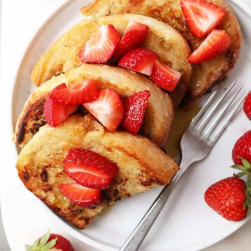 Classic Vegan French Toast with sliced strawberries and maple syrup.