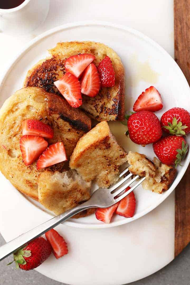 Classic Vegan French Toast with sliced strawberries and a fork.