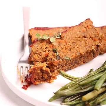 Two slices of vegan meatloaf on a white plate