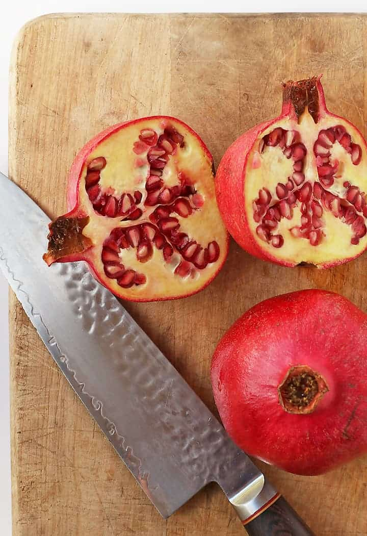 Pomegranate cut open on a cutting board with a knife.