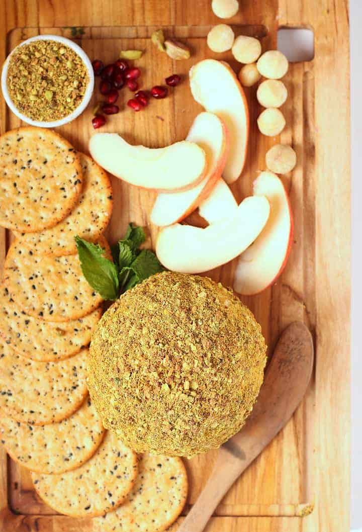 Vegan Cheese Ball covered on a cutting board with apples and crackers.