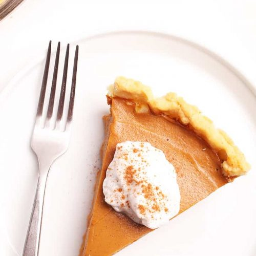 Slice of vegan Pumpkin Pie with coconut whipped cream and cinnamon.