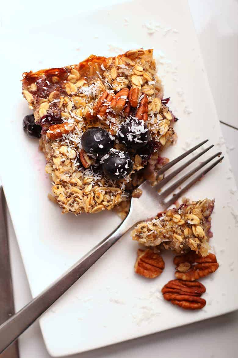 Close up of vegan baked oatmeal on a white plate with a fork.