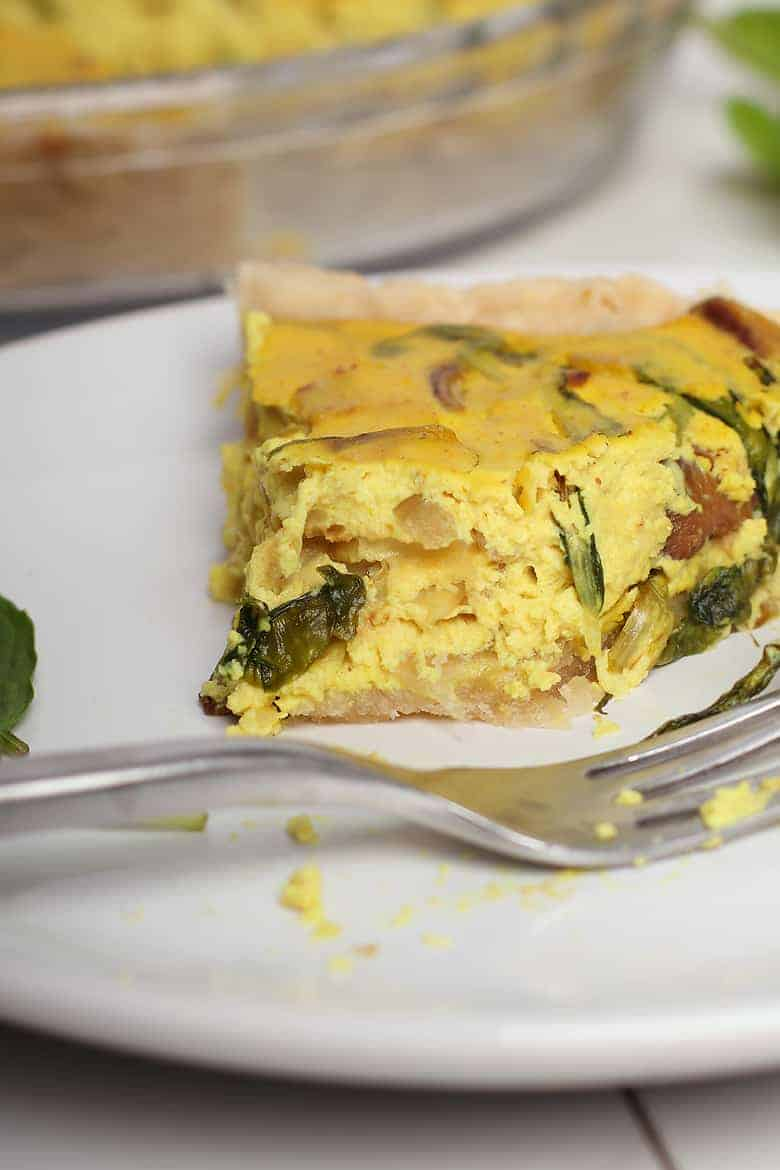 Slice of vegan quiche with a bite
