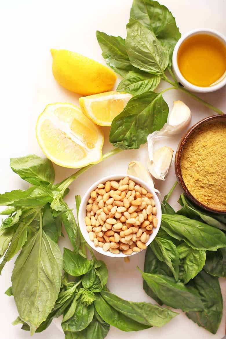 Lemon, basil, and pine nuts on a cutting board