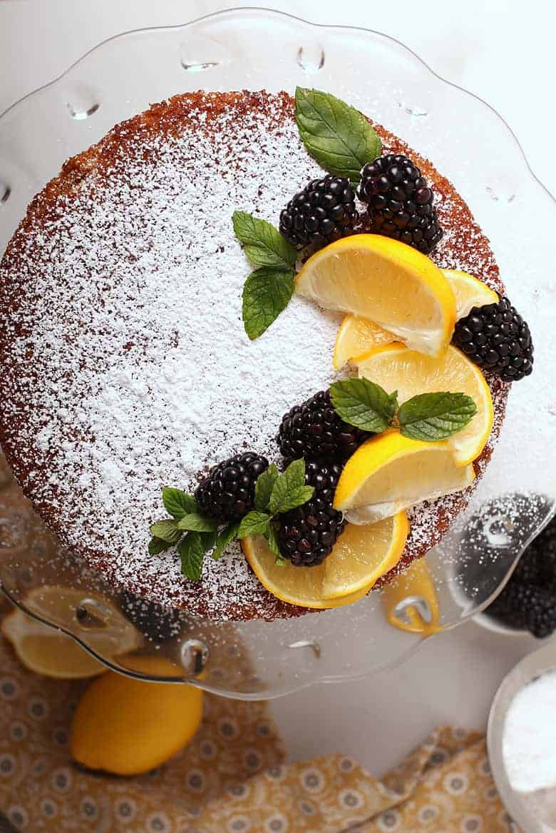 Overhead shot of vegan olive oil cake with lemons, blackberries, and mint.
