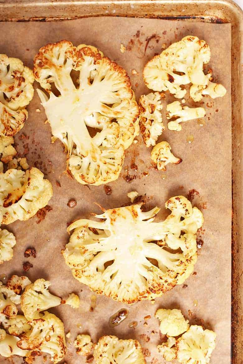 Cooked cauliflower steaks on a baking sheet