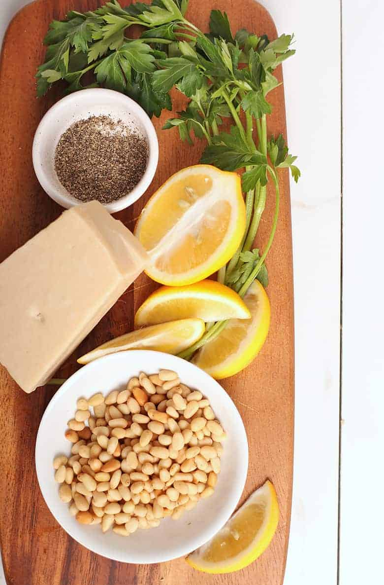 lemon, parsley, pine nuts, and pepper on a wooden board.