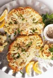 Two cauliflower steaks on silver platter
