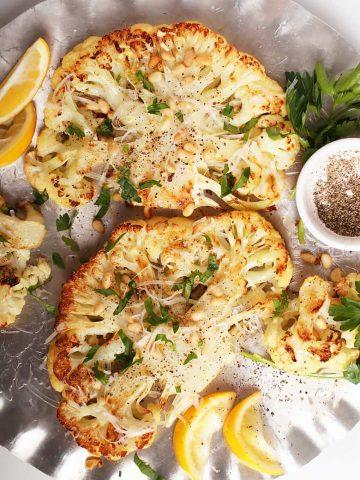Two cauliflower steaks on silver platter