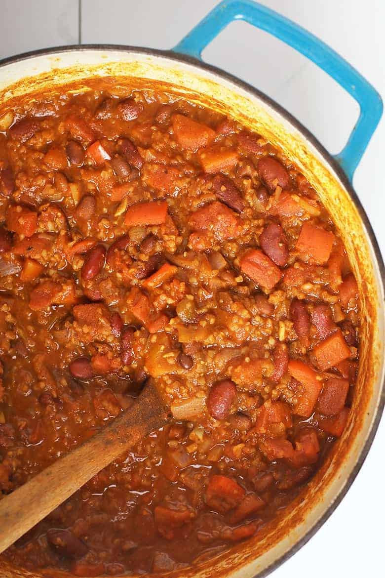 vegan chili in a large soup pot with a wooden spoon