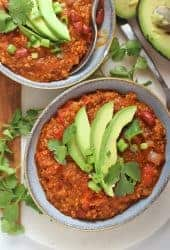Two bowls of vegan chili with avocado and cilantro