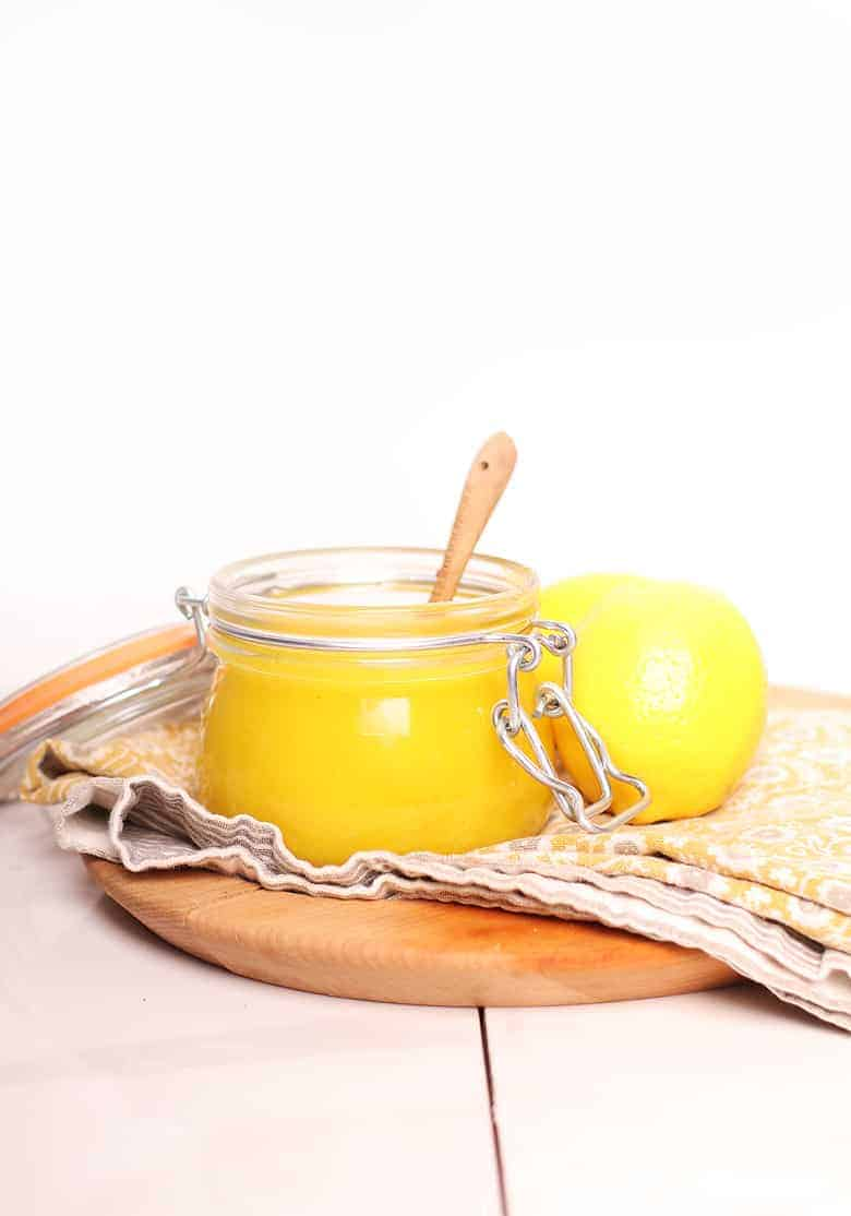 Jar of vegan lemon curd on a brown platter
