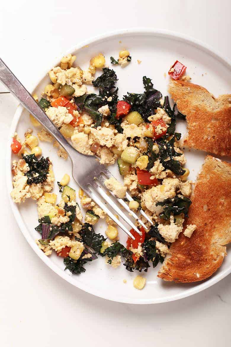 Tofu scramble on a white plate with a fork