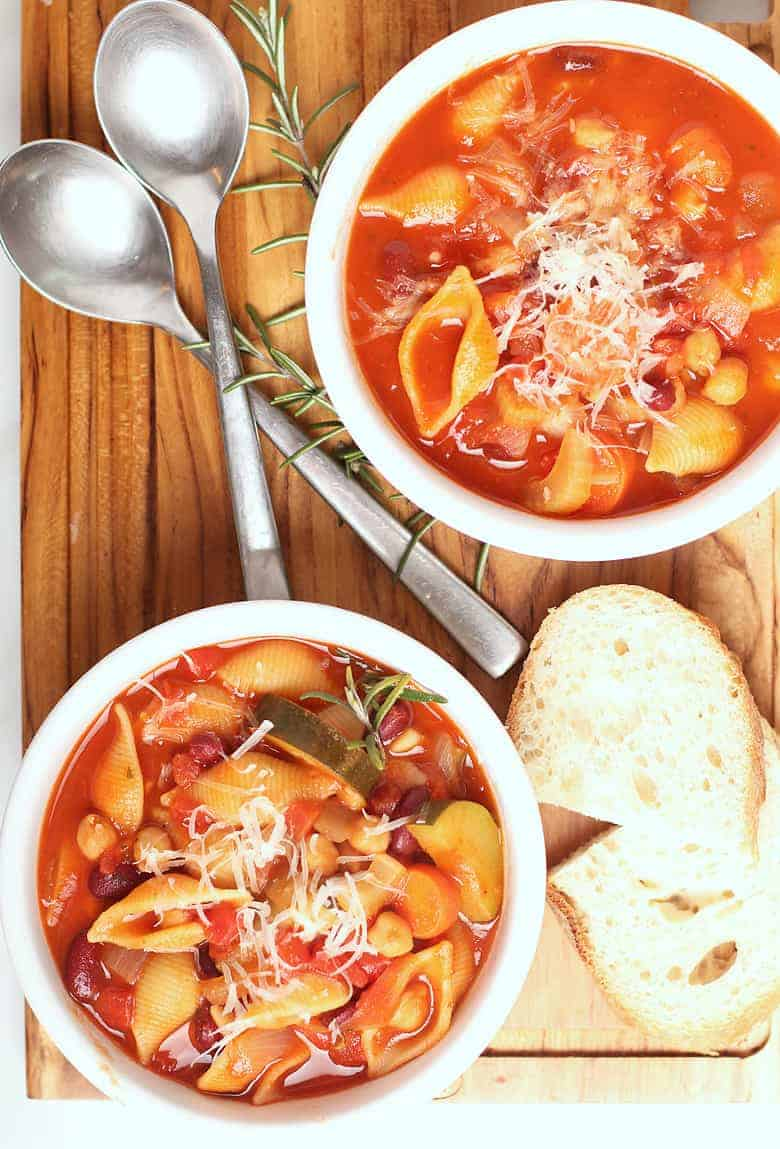 Minestrone soup in a white bowl with spoons