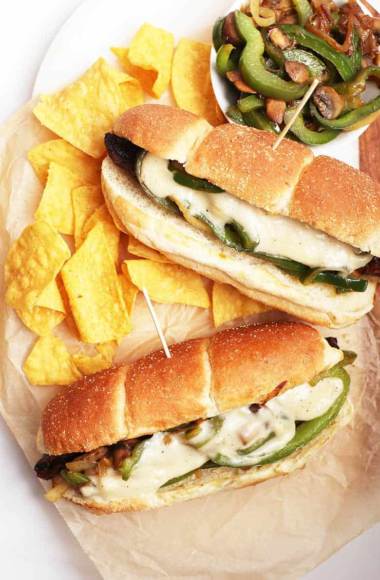 Vegan Philly Cheesecake sandwiches on platter with chips
