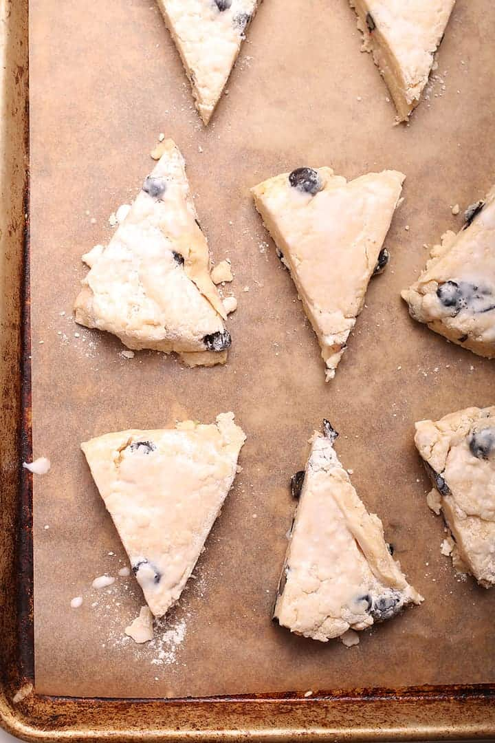 Unbaked blueberry scones on a baking sheet