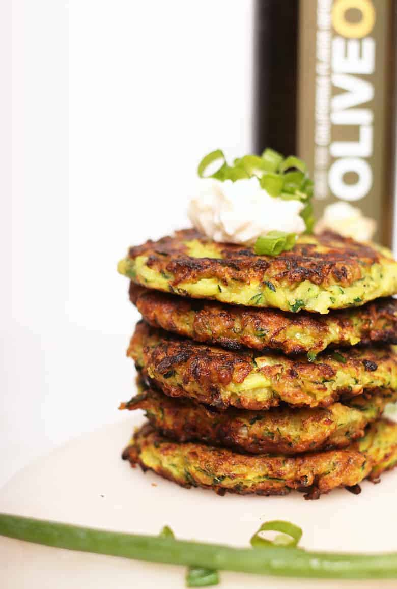Stack of vegan zucchini fritters with sour cream
