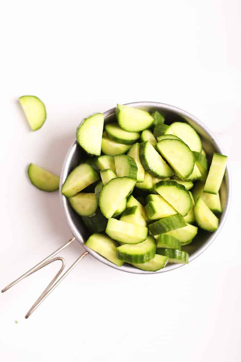 Chopped cucumbers in a metal bowl