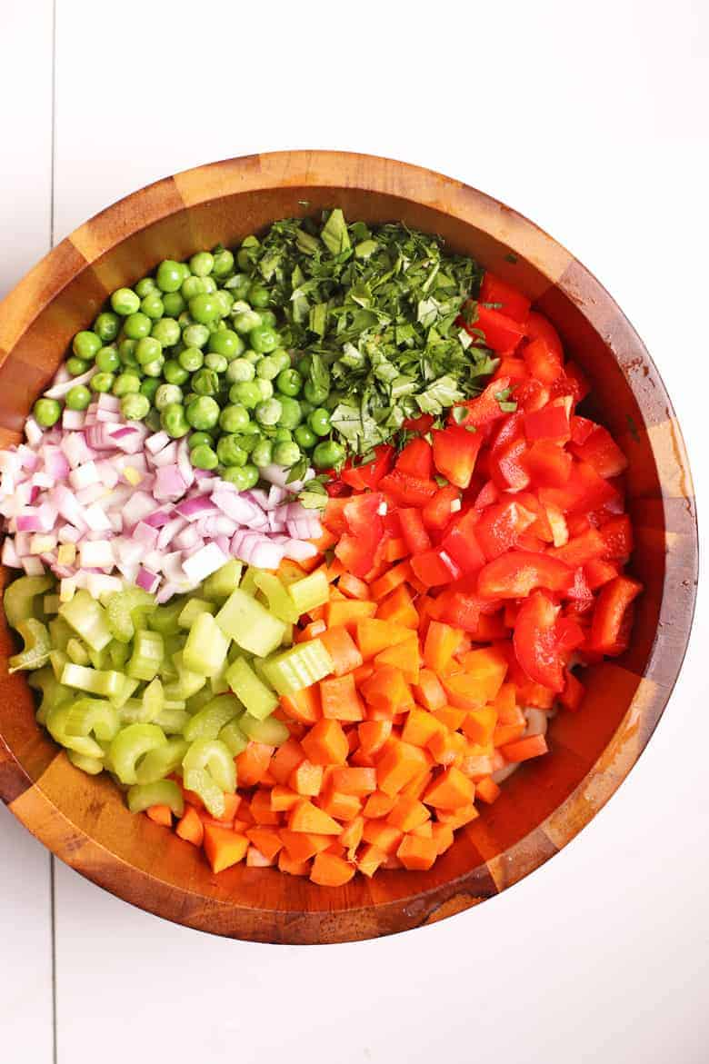 Carrots, celery, onions, peas, and bell pepper in a wooden bowl