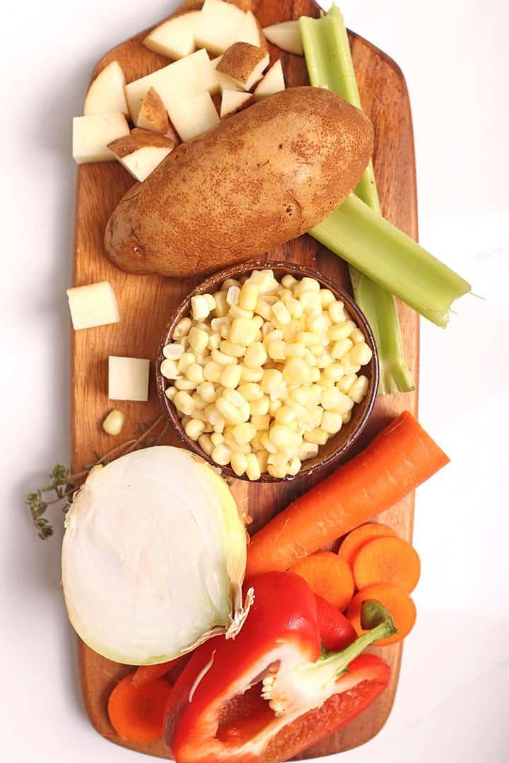 Ingredients for vegan corn chowder on cutting board