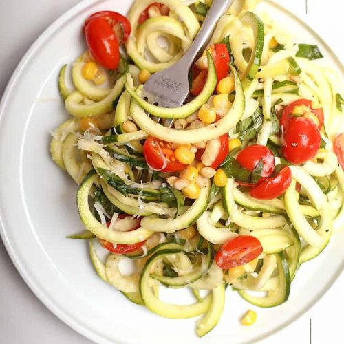 Zucchini noodle salad on white plate