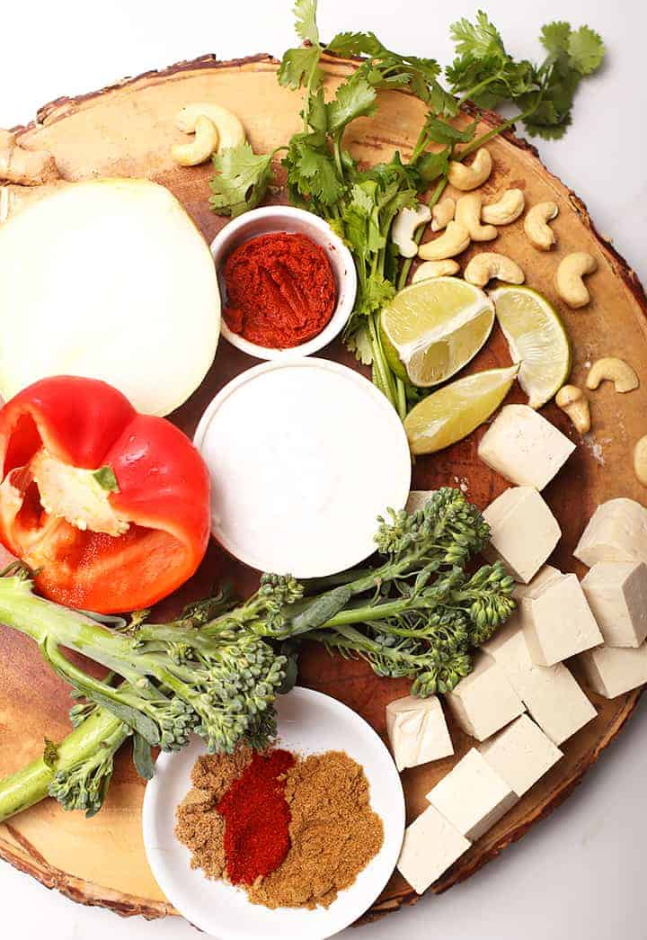 Spices, vegetables, and tofu on wooden platter