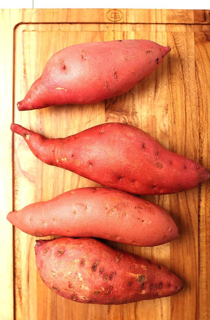 Four sweet potatoes on cutting board