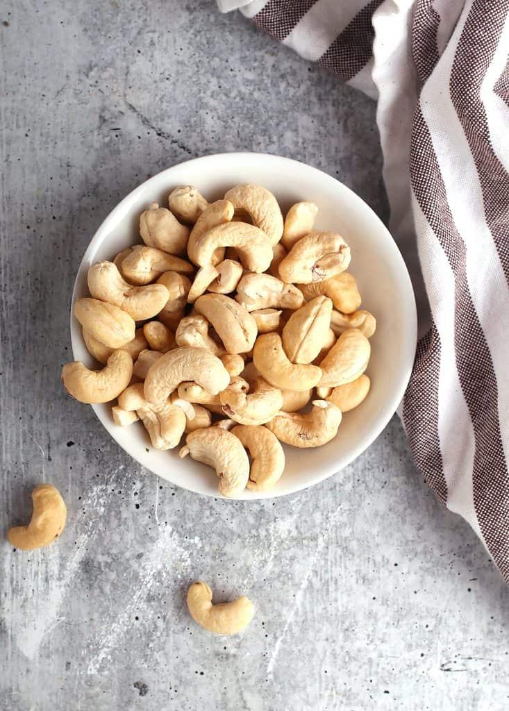 Small white bowl of raw cashews