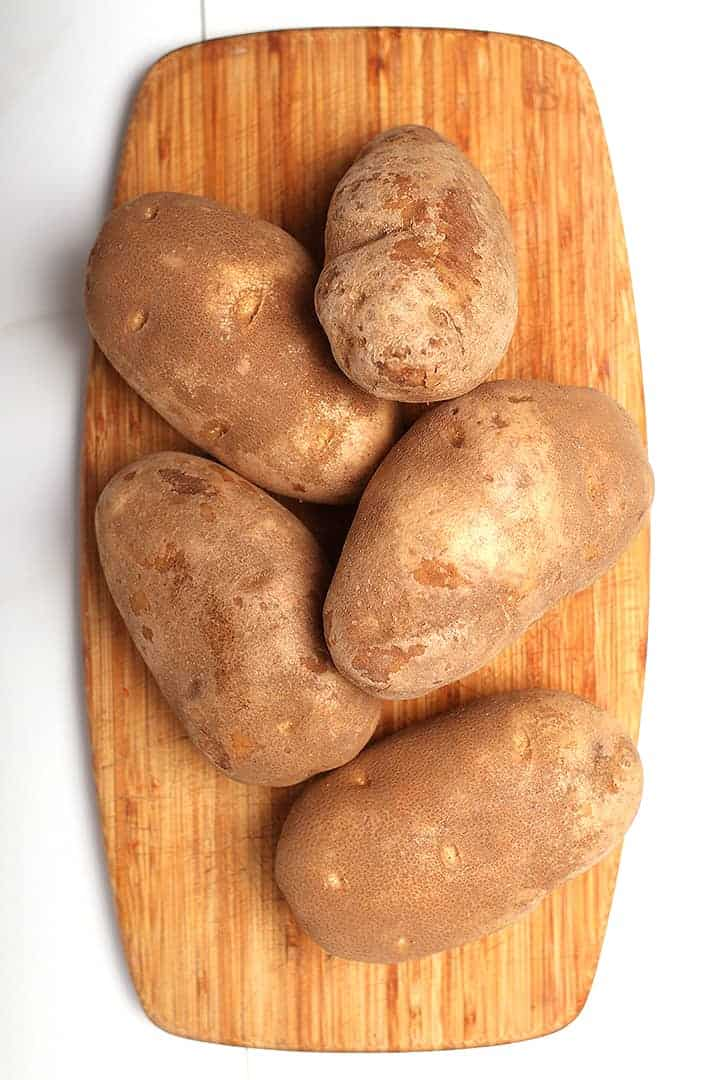 5 russet potatoes on cutting board