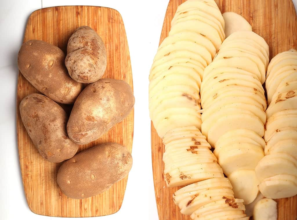 Thinly sliced russet potatoes on a wooden cutting board