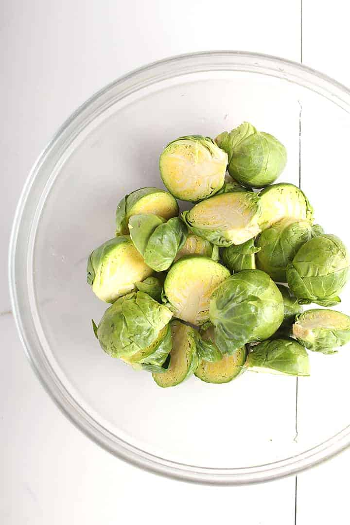 Halved Brussels sprouts in glass bowl