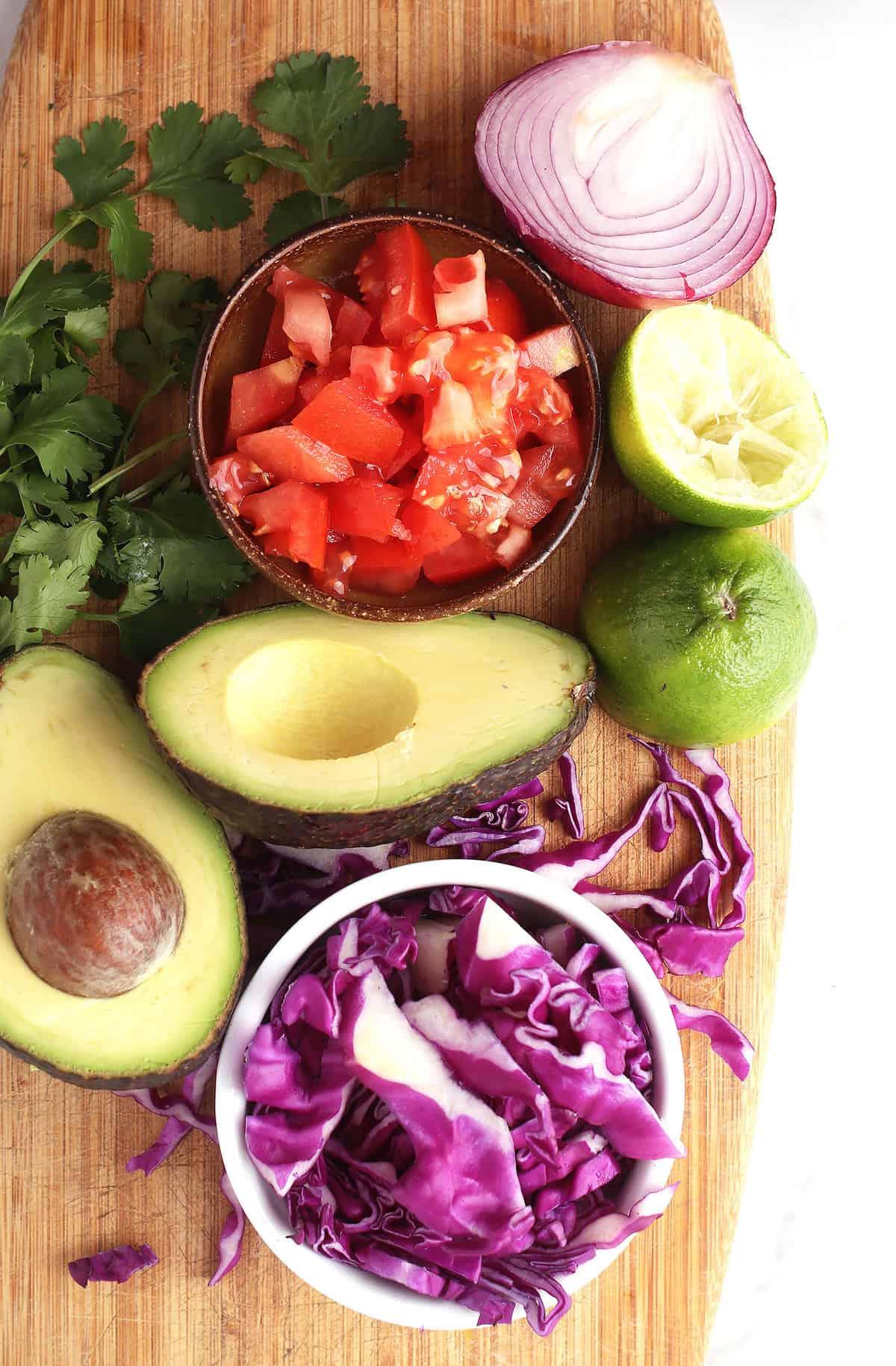 Avocado, tomato, cabbage, and cilantro on cutting board