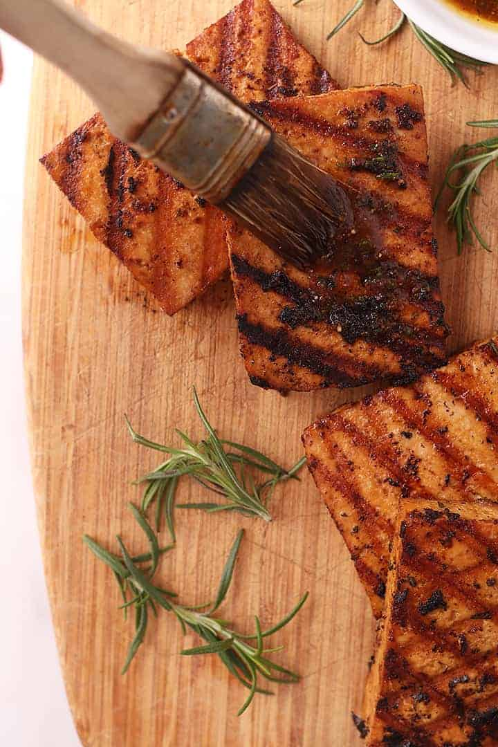 Grilled tofu on cutting board with rosemary