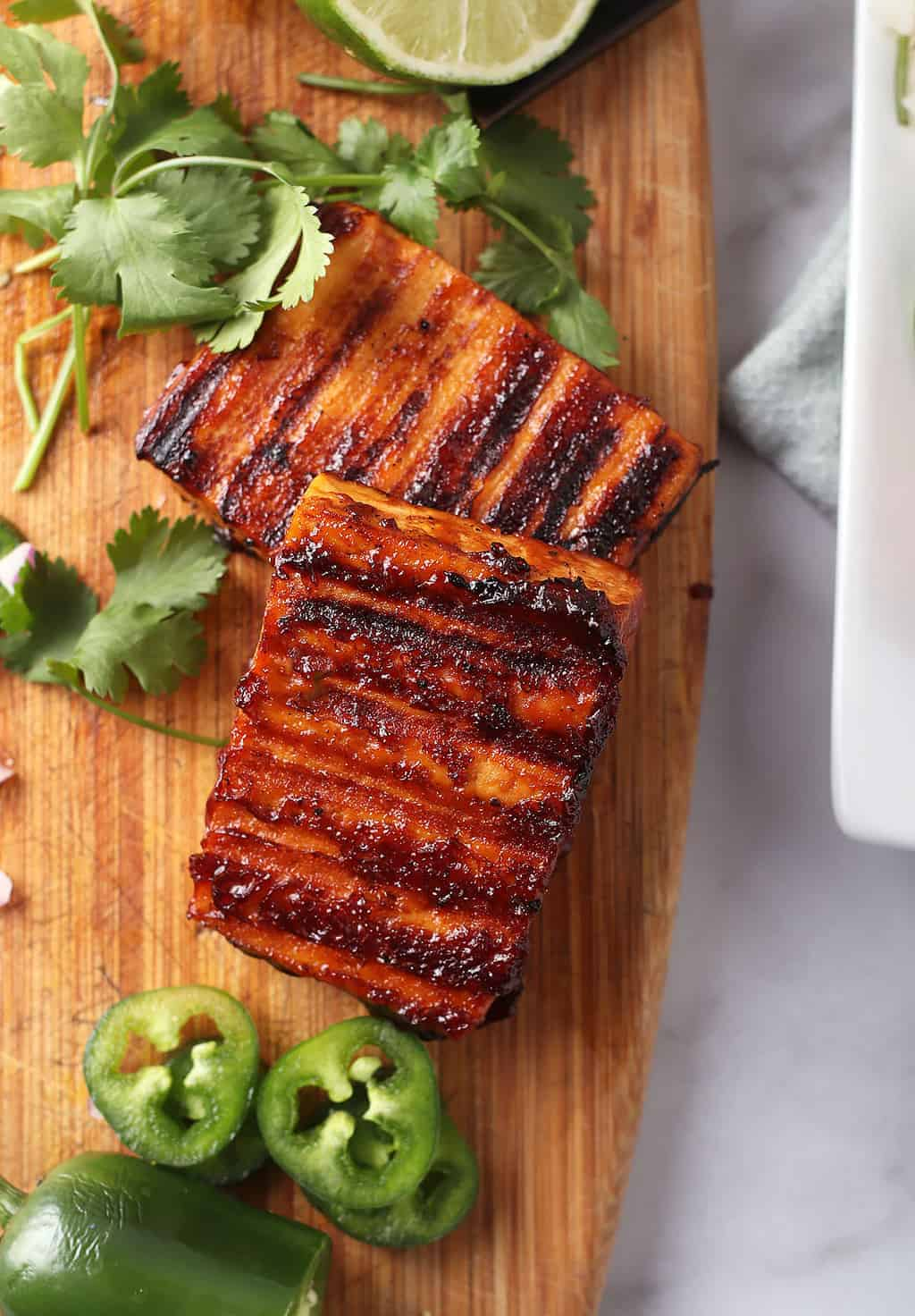 Grilled tofu steaks on wooden cutting board