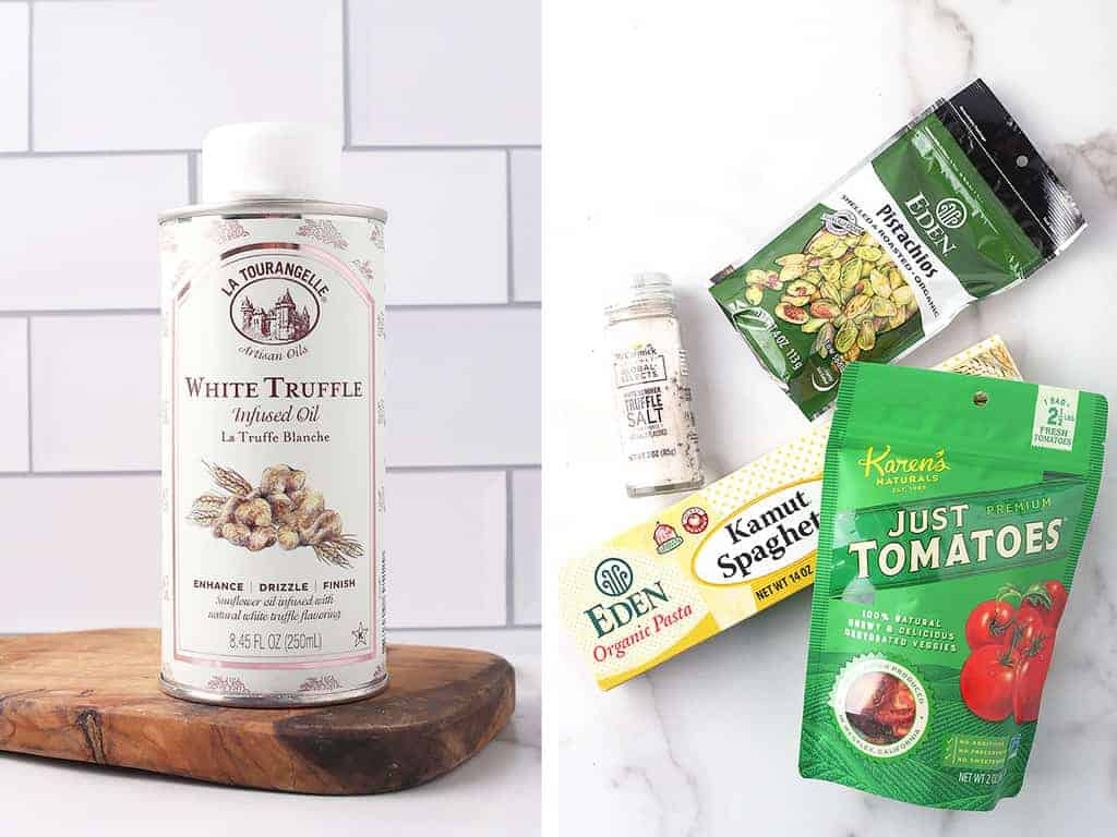 Truffle oil, sun-dried tomatoes, pasta, and pistachios on marble tabletop