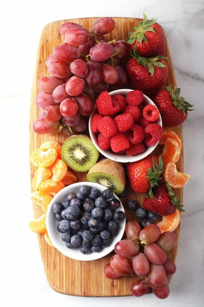 Berries and kiwi on a wooden cutting board