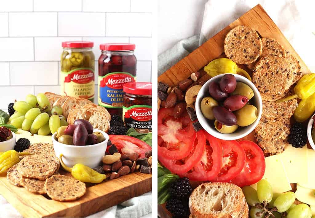 Pickles, tomatoes, bread, and olives on wooden platter
