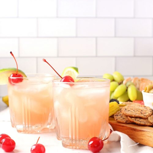 Two pink cocktails with lime and cherries