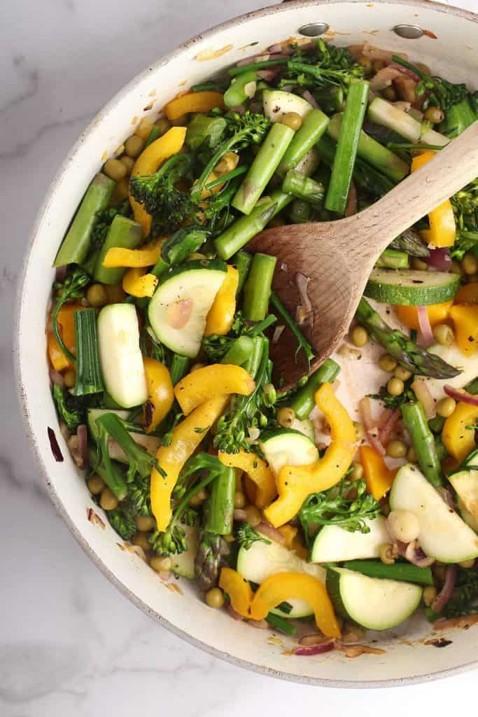 A mixture of spring vegetables in a cast iron skillet