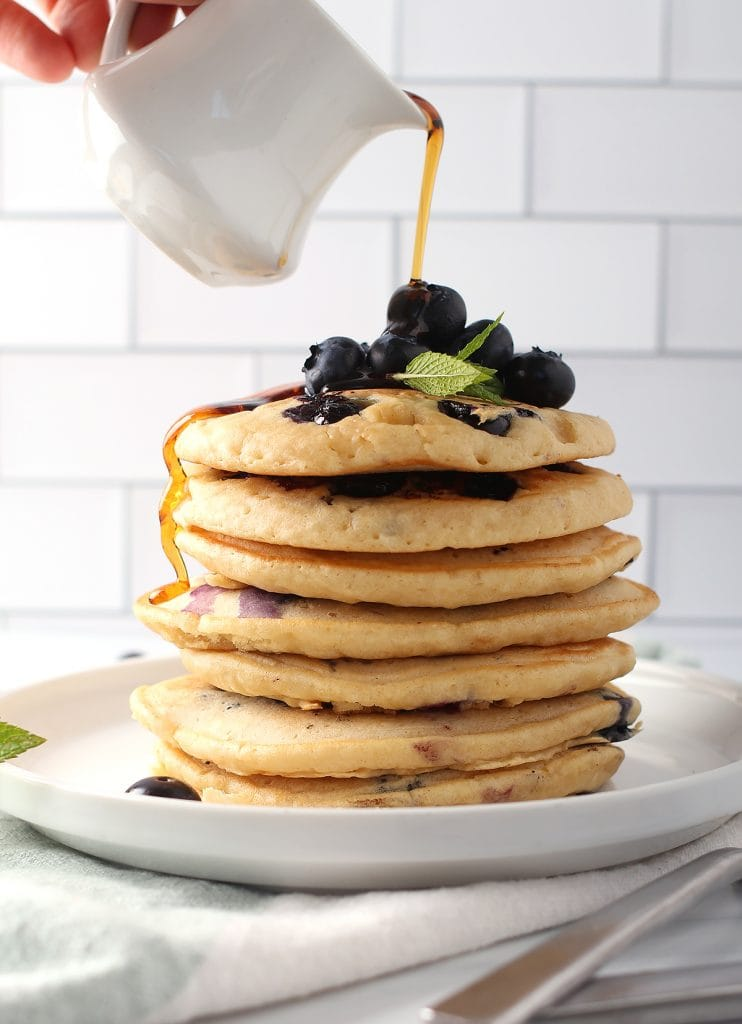 Stack of finished pancakes with fresh maple syrup