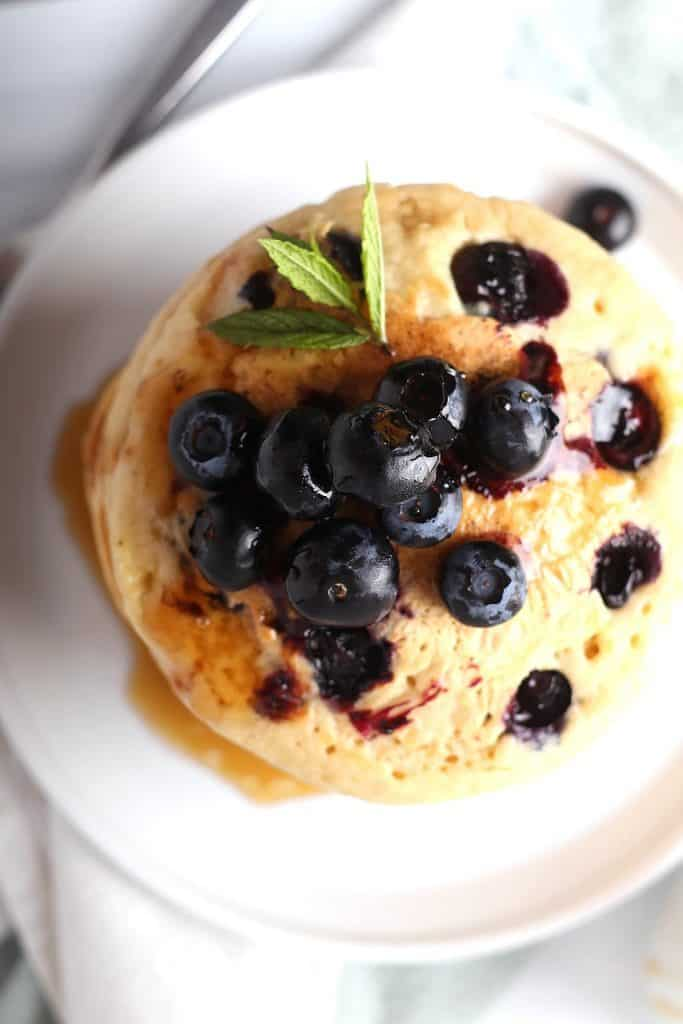 Overhead shot of blueberry pancakes on a white plate