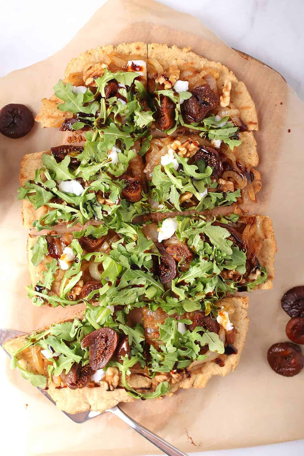 Vegan grilled flatbread topped with arugula and figs