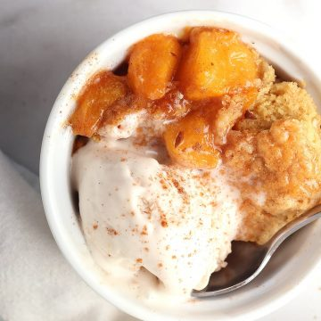 Finished cobbler in a white bowl with vanilla ice cream