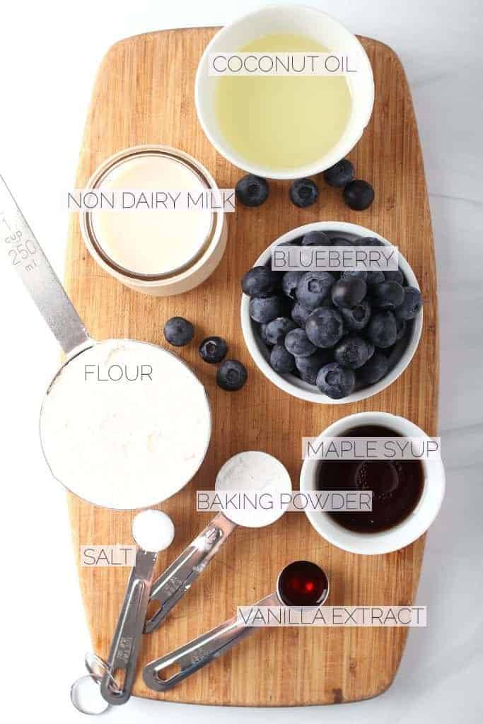 Blueberries, flour, oil, and maple syrup on a wooden board