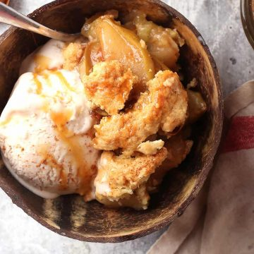 Finished apple cobbler in a brown bowl with ice cream