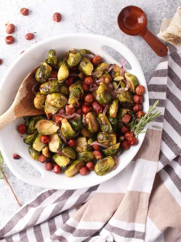Roasted brussels sprouts and hazelnuts in a white bowl